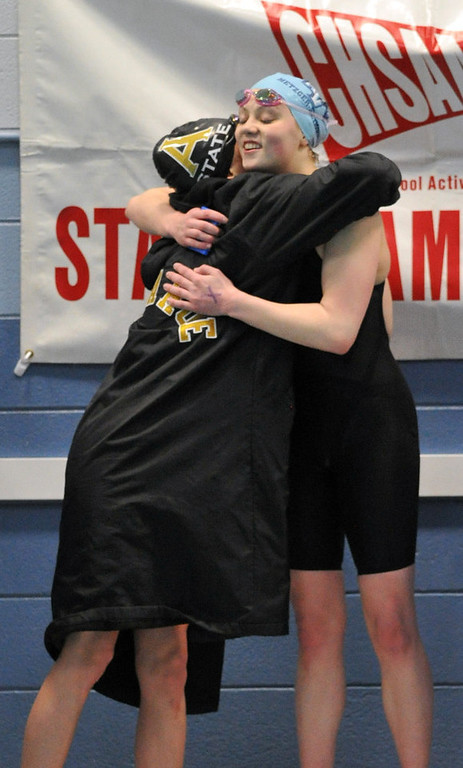 . FORT COLLINS, CO. - FEBRUARY 09: Erin Metzger-Seymour of Ralston Valley High School, right, hugs Ella Moynihan of Arapahoe High School after winning the 200 Yard Freestyle for the 5A State Championship on February 9, 2013 at Edora Pool Ice Center in Fort Collins, Colorado. Moynihan finished the race as 2nd place. (Photo By Hyoung Chang/The Denver Post)