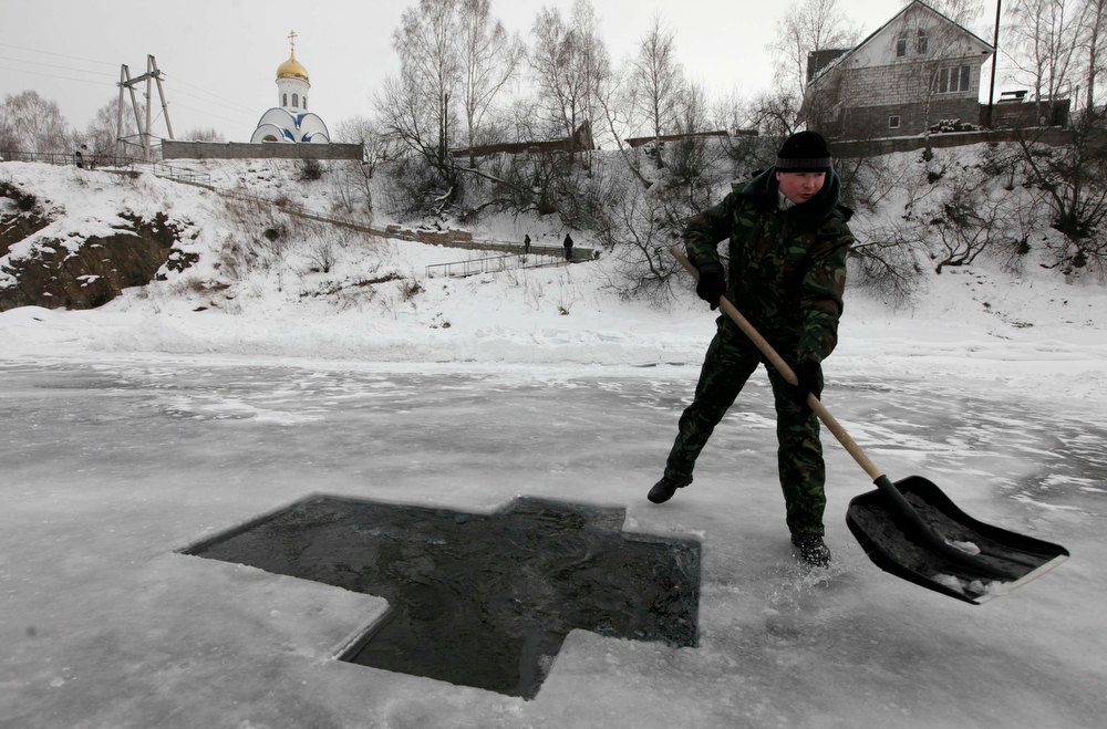 Description of . A worker prepares a cross shaped bathing hole for the forthcoming Russian Orthodox Epiphany celebrations on the Mana river near the village of Ust-Mana, 31 km (19 miles) south of the Siberian city of Krasnoyarsk, January 18, 2013. Russian Orthodox believers will celebrate the religious holiday of Epiphany with a midnight immersion in water after midnight and on the morning of January 19.  REUTERS/Ilya Naymushin