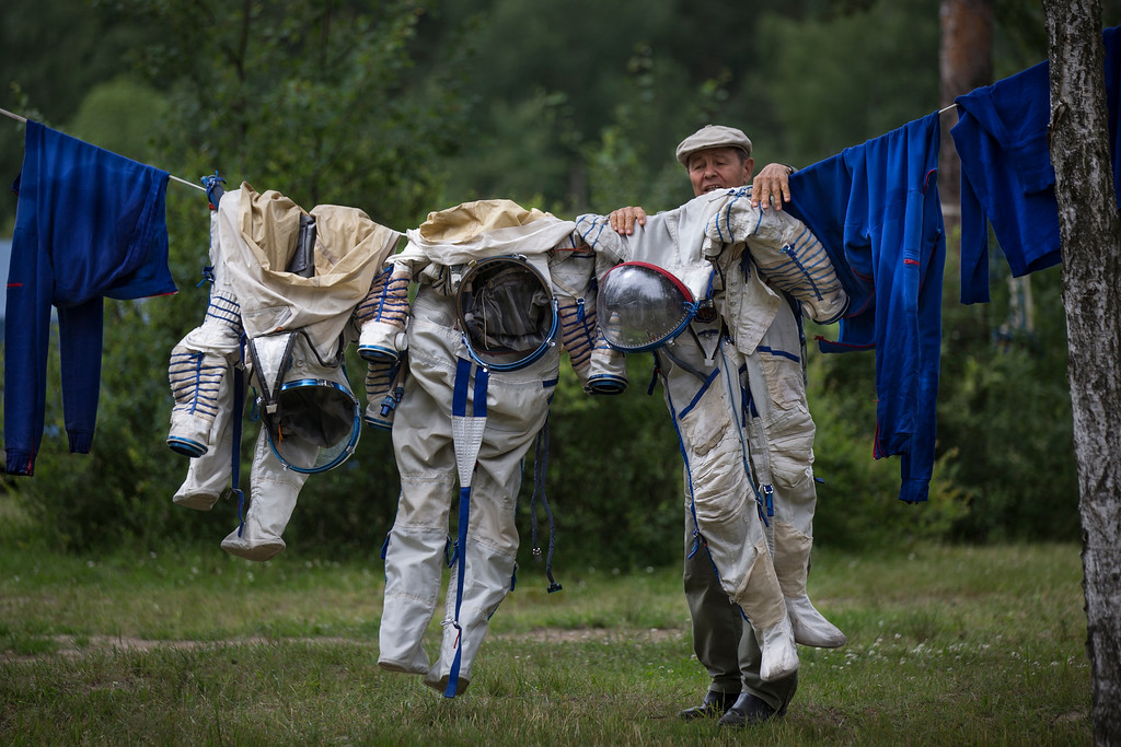 . An employee of the Russian Space Training Center hangs out space suits to dry of Russian cosmonaut Anatoly Ivanishin, NASA\'s U.S. flight engineer Kathleen Rubins and Japanese space agency\'s flight engineer Takuya Onishi after their undergoing training near in Noginsk, 60 km (38 miles) east of Moscow, Russia, Wednesday, July 2, 2014. The training was intended to simulate the capsule landing on water. (AP Photo/Alexander Zemlianichenko, File)