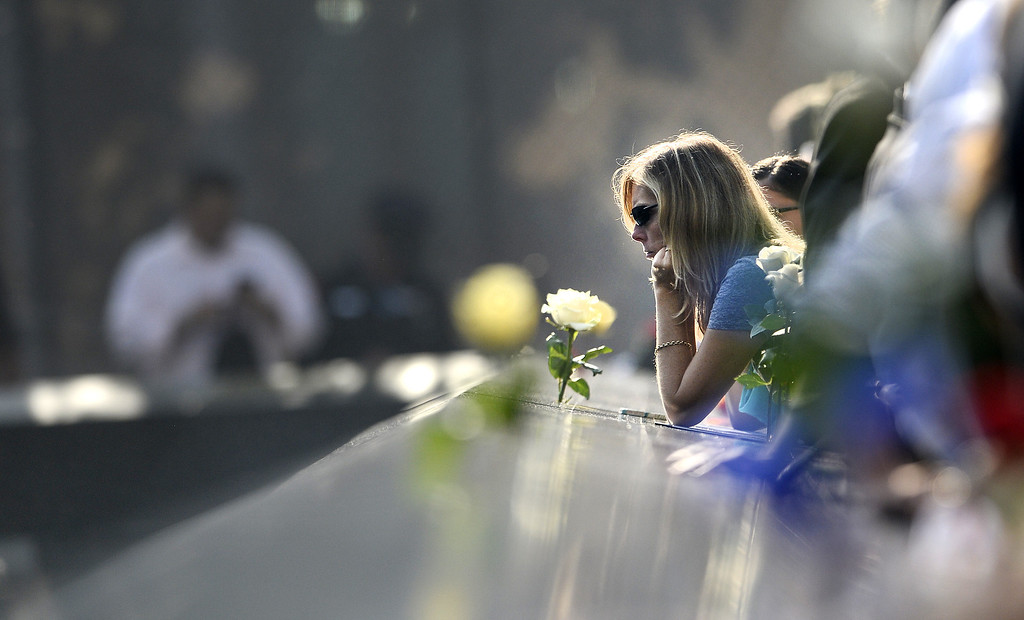 . A woman pauses along the edge of the North Pool at the 9/11 Memorial during ceremonies for the twelfth anniversary of the terrorist attacks on lower Manhattan at the World Trade Center site on September 11, 2013 in New York City.   (Photo by Justin Lane-Pool/Getty Images)