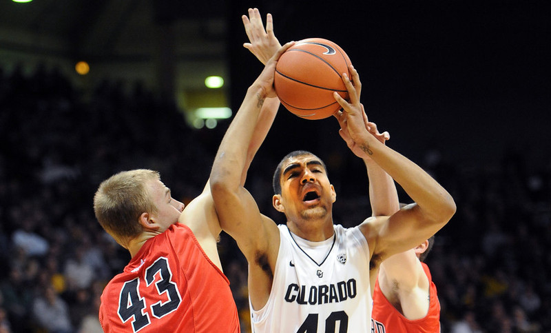 . Josh Scott of CU goes to the basket on Nate Sikma of Hartford, during the first half of the December 29, 2012 game in Boulder. (Cliff Grassmick / Daily Camera) December 29, 2012