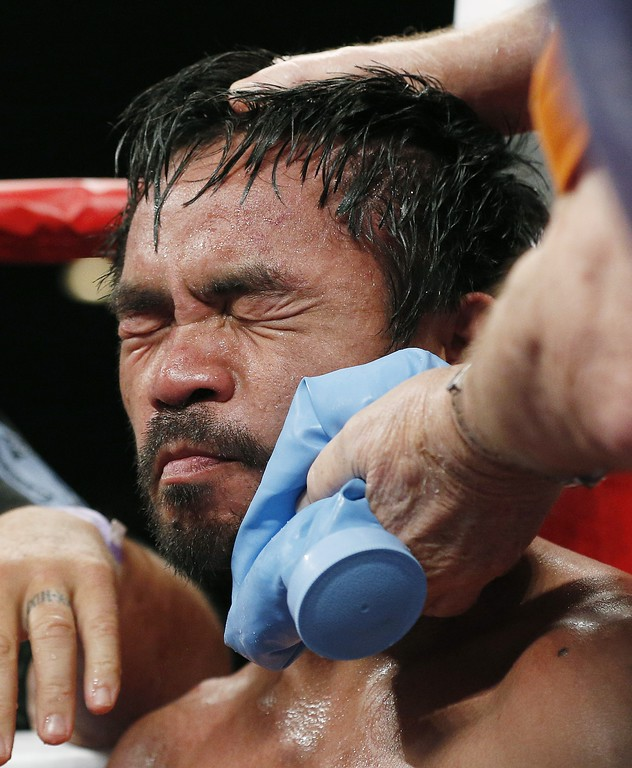 . Manny Pacquiao, from the Philippines, is helped in his corner between rounds during his welterweight title fight against Floyd Mayweather Jr. on Saturday, May 2, 2015 in Las Vegas. (AP Photo/Isaac Brekken)
