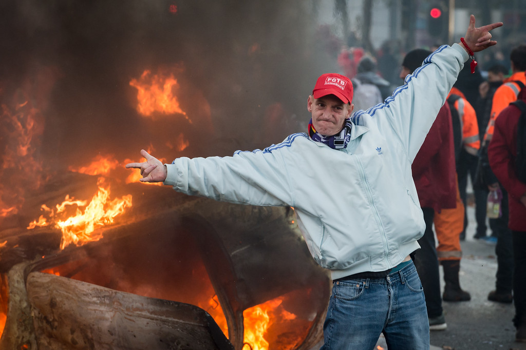 . A protestor stands in front of a burning car during a national trade union demonstration in Brussels, Thursday Nov. 6, 2014. (AP Photo/Geert Vanden Wijngaert)