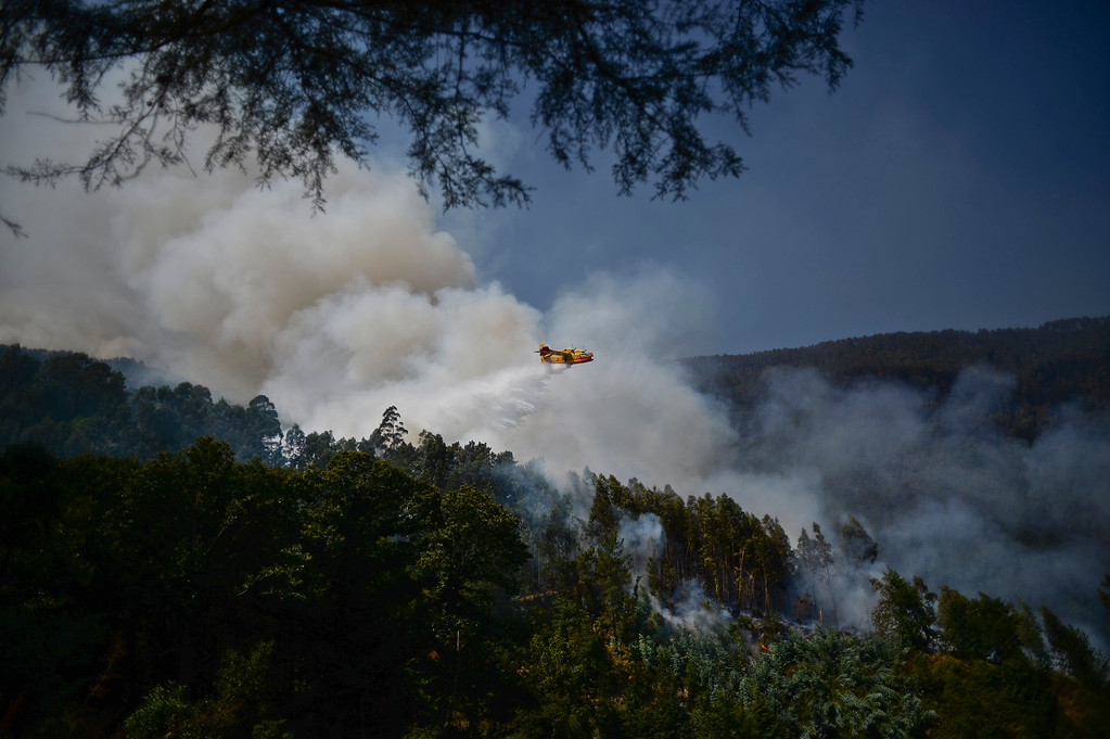 . Firefighting aircraft drop water to try and to extinguish a wildfire around Caramulo, central Portugal, on August 30, 2013.   AFP PHOTO / PATRICIA DE MELO MOREIRA/AFP/Getty Images