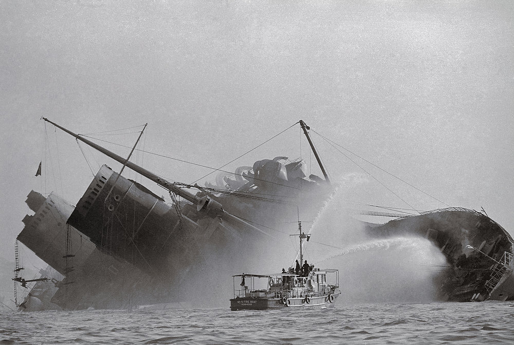 Description of . A fireboat sprays water on the still-burning blackened hull of the former Queen Elizabeth after she rolled over following a 24-hour fire. The Queen, newly renamed Seawise University, caught fire while being refitted as a seagoing university. (Copyright Bettmann/Corbis / AP Images)