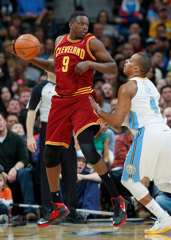 . Cleveland Cavaliers forward Luol Deng, left, of Sudan, pulls in a loose ball as Denver Nuggets guard Randy Foye covers in the fourth quarter of the Cavaliers\' 117-109 victory in an NBA basketball game in Denver on Friday, Jan. 17, 2014. (AP Photo/David Zalubowski)