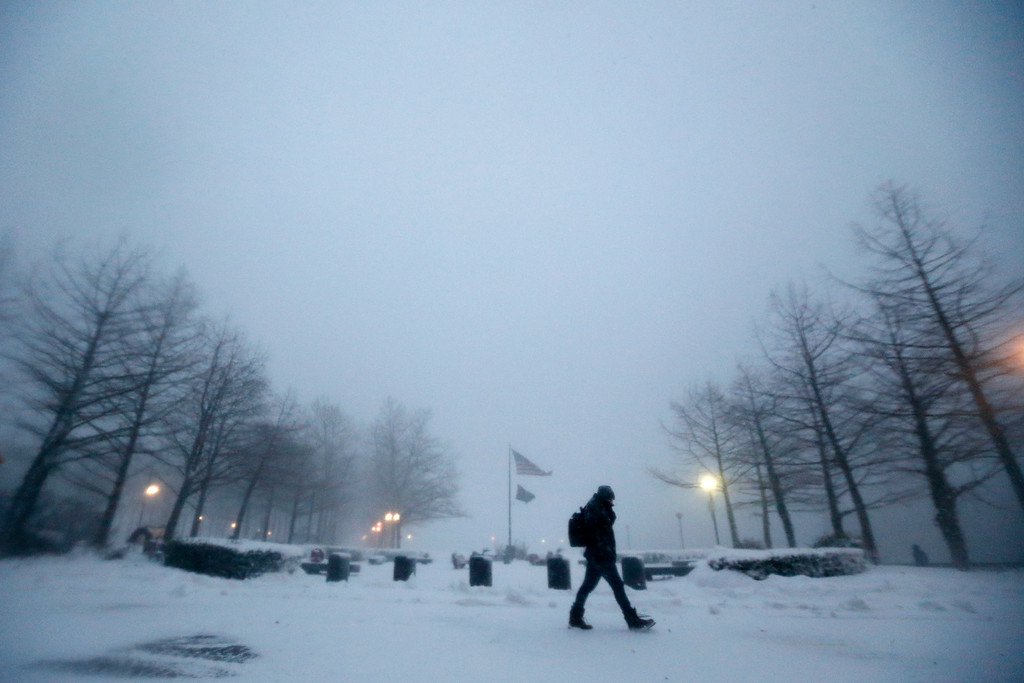 . A person walks on a snow-covered path at Pier A Park during a snowstorm, Saturday, Jan. 23, 2016, in Hoboken, N.J. Towns across the state are hunkering down during a major snowstorm that hit overnight. (AP Photo/Julio Cortez)