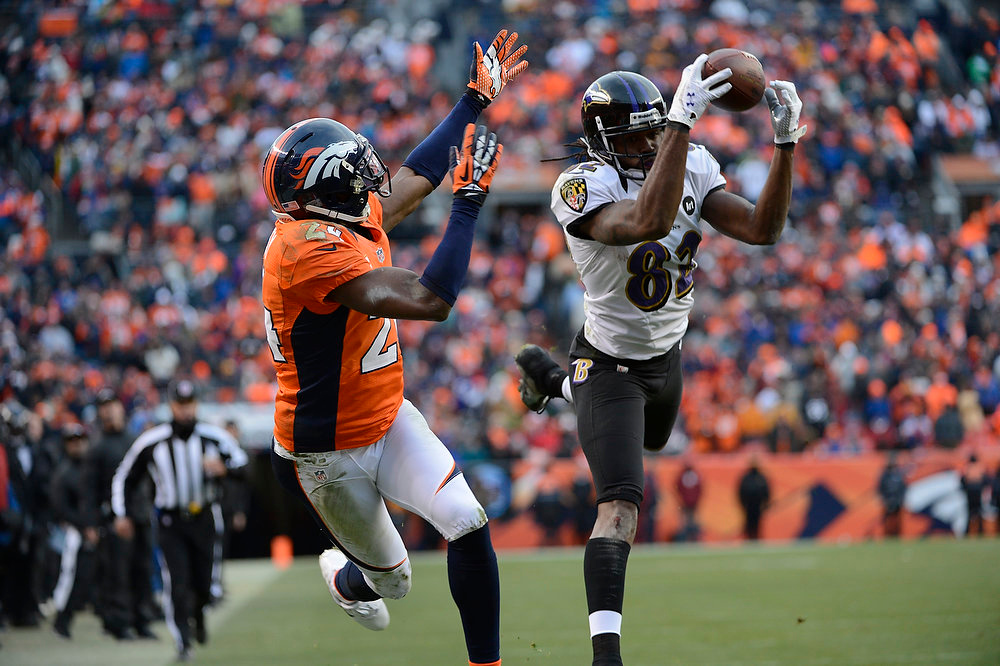 Description of . Baltimore Ravens wide receiver Torrey Smith (82) pulls in a pass and scores a touchdown against Denver Broncos cornerback Champ Bailey (24) during the second quarter.  The Denver Broncos vs Baltimore Ravens AFC Divisional playoff game at Sports Authority Field Saturday January 12, 2013. (Photo by Hyoung Chang,/The Denver Post)