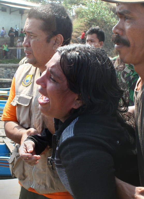 . In this photograph taken on July 24, 2013 a female survivor (C) grieves while assisted by Indonesian rescuers upon her arrival at the wharf of Cidaun, West Java on July 24, 2013 after an Australia-bound boat carrying asylum-seekers sank off the Indonesian coast, leaving at 11 confirmed dead. Rescuers continued searching the seas off Indonesian for survivors. Police have said around 200 were aboard, but an asylum-seeker has said 250 people, mostly Sri Lankans, made the perilous  journey.  AFP PHOTOSTR/AFP/Getty Images
