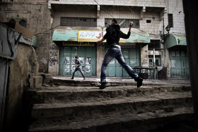 . Palestinian protesters throw stones towards Israeli troops during clashes in the old city of Hebron on March 1, 2013 following a protest demanding the reopening of Shuhada Street, the one-time heart of the city. Flanked by a handful of Jewish settlement enclaves, Shuhada Street was partially closed off in 1994 after local settler Baruch Goldstein opened fire on Muslim worshippers at the city\'s Al-Ibrahimi mosque, killing 29 of them. MARCO LONGARI/AFP/Getty Images