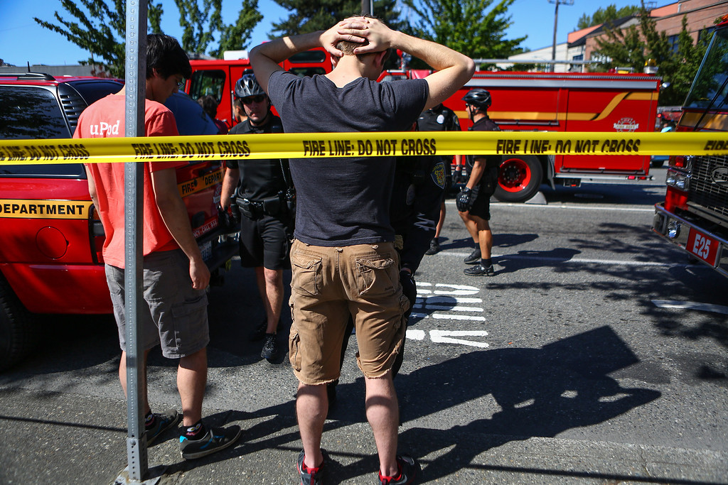 . Students are searched by Seattle police after a shooting at Seattle Pacific University on Thursday, June 5, 2014, in Seattle. A lone gunman armed with a shotgun opened fire  in a building at the small Seattle university, fatally wounding one person and injuring three others before a student subdued him with pepper spray as he tried to reload, Seattle police said. (AP Photo/seattlepi.com, Joshua Trujillo)