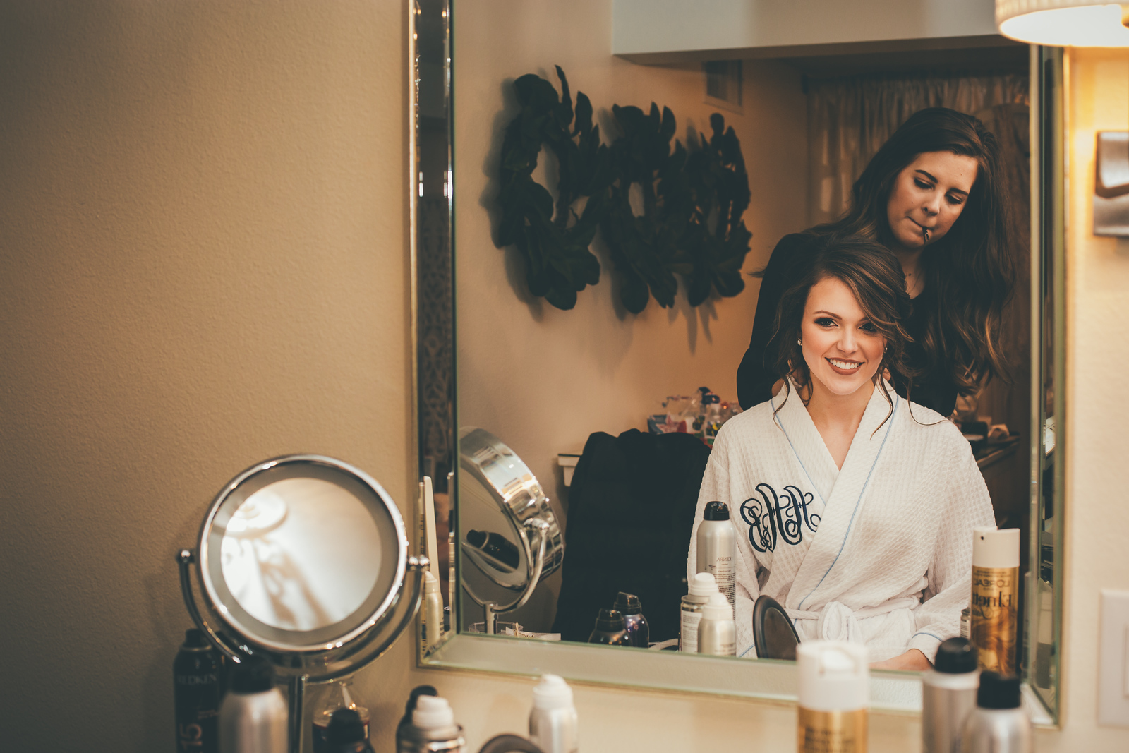 A bride looking in the mirror smiling as she gets her hair done