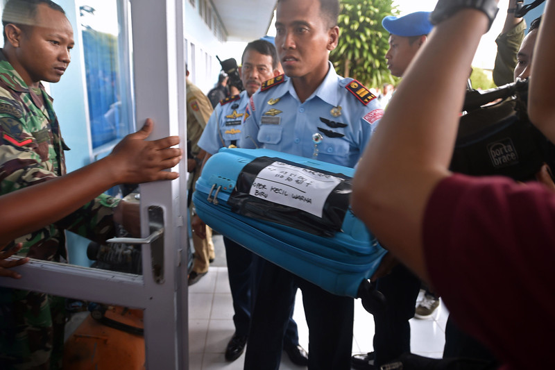 . A member of the Indonesian air force carries an item retrieved from the Java sea during search and rescue operations for the missing AirAsia flight QZ8501, in Pangkalan Bun, Central Kalimantan on December 30, 2014. The hunt for a missing AirAsia passenger plane appeared over on December 30 as wreckage and dozens of bodies were spotted at sea off Indonesia, prompting raw scenes of emotion from sobbing relatives of the 162 people aboard. BAY ISMOYO/AFP/Getty Images