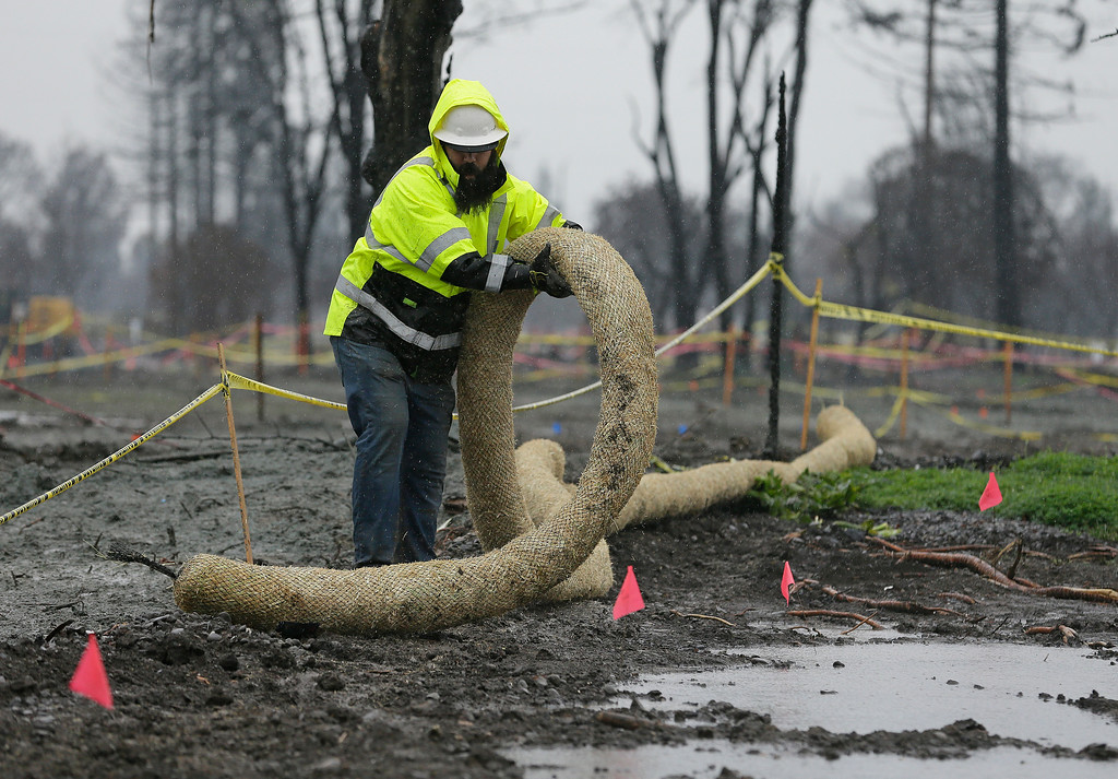 . A worker lays out a roll of wattle for erosion control in the wildfire damaged Coffey Park neighborhood Monday, Jan. 8, 2018, in Santa Rosa, Calif. Storms brought rain to California on Monday and increased the risk of mudslides in fire-ravaged communities in devastated northern wine country and authorities to order evacuations farther south for towns below hillsides burned by the state\'s largest-ever wildfire. (AP Photo/Eric Risberg)
