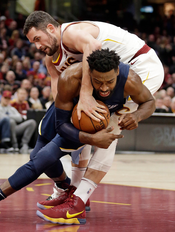 . Memphis Grizzlies\' Tyreke Evans becomes entangled with Cleveland Cavaliers\' Kevin Love, top, in the first half of an NBA basketball game, Saturday, Dec. 2, 2017, in Cleveland. (AP Photo/Tony Dejak)