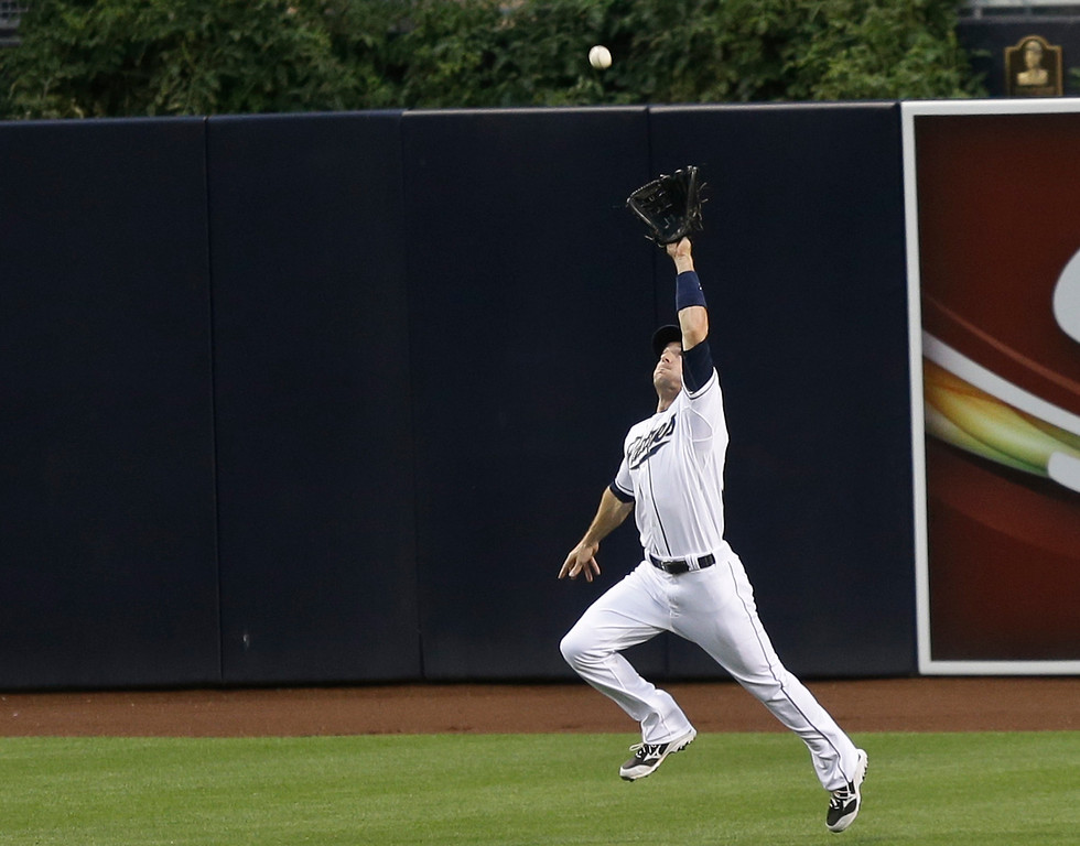 . San Diego Padres center fielder Chris Denorfia gets back to make a catch on a drive by Colorado Rockies\' Jonathan Herrera in the second inning of a baseball game in San Diego, Wednesday, July 10, 2013. Todd Helton scored from third.  (AP Photo/Lenny Ignelzi)