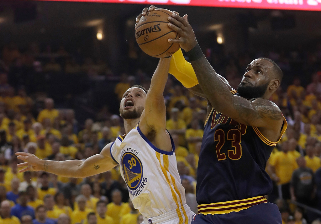 . Cleveland Cavaliers forward LeBron James (23) grabs a rebound against Golden State Warriors guard Stephen Curry (30) during the first half of Game 1 of basketball\'s NBA Finals in Oakland, Calif., Thursday, June 1, 2017. (AP Photo/Marcio Jose Sanchez)