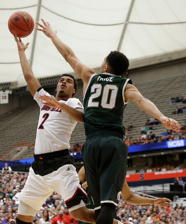 . Louisville\'s Quentin Snider (2) drives past Michigan State\'s Travis Trice (20) during the first half of a regional final in the NCAA men\'s college basketball tournament Sunday, March 29, 2015, in Syracuse, N.Y. (AP Photo/Seth Wenig)
