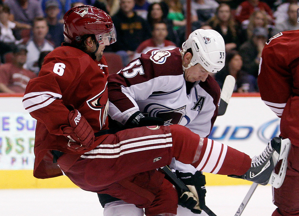 . Phoenix Coyotes defenseman David Schlemko, left, is checked by Colorado Avalanche left winger Cody McLeod, right, in the first period of NHL hockey game, Saturday, April 6, 2013, in Glendale, Ariz. (AP Photo/Paul Connors)