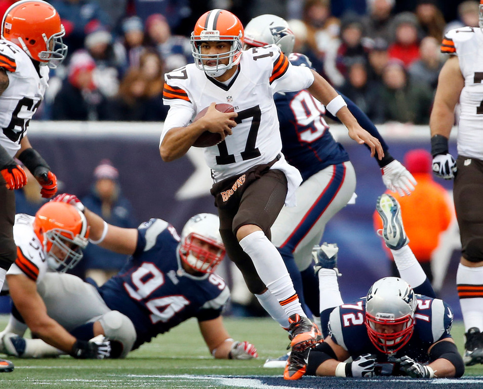 . Cleveland Browns quarterback Jason Campbell (17) runs from New England Patriots defenders Chris Jones (94) and Joe Vellano (72) in the first quarter of an NFL football game on Sunday, Dec. 8, 2013, in Foxborough, Mass. (AP Photo/Elise Amendola)