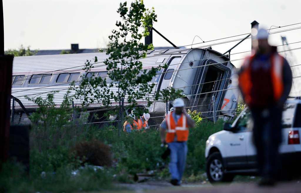 . Emergency personnel walk near the scene of a deadly train wreck, Wednesday, May 13, 2015, in Philadelphia. An Amtrak train headed to New York City derailed and crashed in Philadelphia on Tuesday night. (AP Photo/Mel Evans)