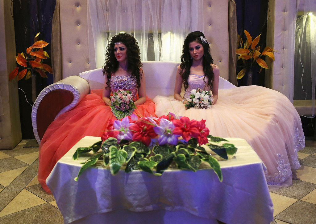 . Kurdish brides Halbast Khalili, 21, (L), and Mezgin Murat, 21, (C), sit on the chez lounge of honor during a wedding reception without their grooms on November 11, 2015 in Qamishli, in the autonomous region of Rojava, Syria. They married their husbands in absentia two months after the brothers successfully immigrated to Germany in the arduous journey as refugees. The women plan to join their husbands in Europe once their immigration documents have been processed.  (Photo by John Moore/Getty Images)