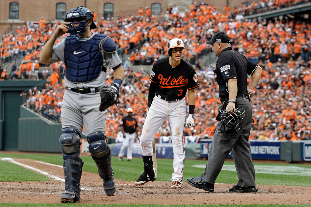 . Baltimore Orioles\' Ryan Flaherty (3) speaks with home plate umpire Scott Barry after striking out looking to end the sixth inning of Game 2 in baseball\'s AL Division Series in Baltimore, Friday, Oct. 3, 2014. At left is Detroit Tigers catcher Alex Avila. (AP Photo/Patrick Semansky)