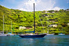 Large and luxurious sailboats anchored infront of beautiful tropical island.