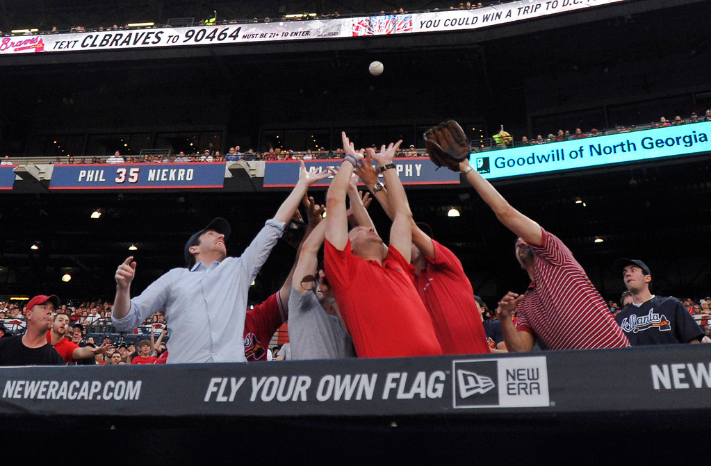 . Baseball fans behind the Atlanta Braves dugout reach for a foul ball hit by Atlanta\'s Chris Johnson during the second inning of a baseball game against the Colorado Rockies Friday, May 23, 2014, in Atlanta. (AP Photo/David Tulis)