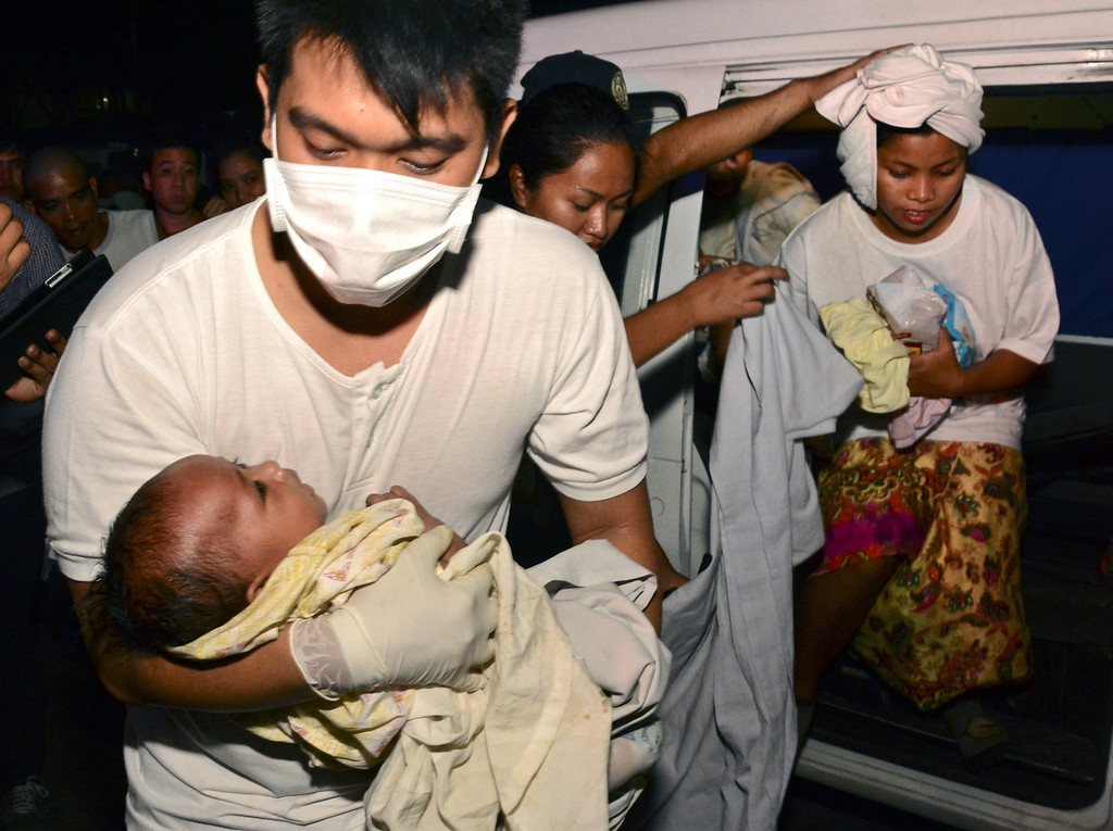 . A medic carries rescued three-month old Trisia Mae Kumaro along with her mother (back) after they were rescued from a sea collision in Cebu, central Philippines on August 16, 2013. A ferry in the Philippines sank after colliding with a cargo ship August 16, leaving at least 17 people dead and many others feared missing, while nearly 600 were rescued, authorities said.  AFP PHOTO-/AFP/Getty Images