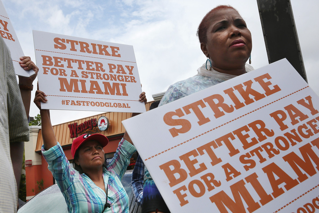 . Maria Mejia (L) and others join in a fast food workers protest in front of a Wendy\'s restaurant on May 15, 2014 in Miami, Florida. The protesters were part of a nation wide movement to show support for fast food workers wages of $15 an hour and what they say is a need for better working conditions.  (Photo by Joe Raedle/Getty Images)