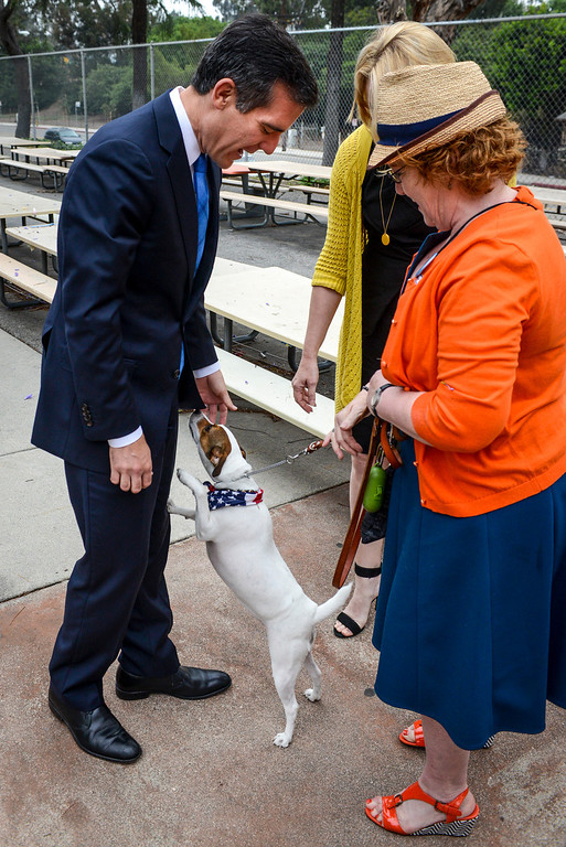 . Mayoral candidate Eric Garcetti and his wife Amy are greeted by voter Deborah Murphy and her dog Fiona at Allesandro Elementary school in Los Angeles early Tuesday morning.  Los Angeles residents will vote for a new mayor, Garcetti or Wendy Gruel in the citywide election.  Photo by David Crane/Staff Photographer