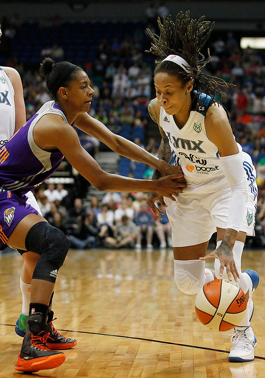 . Minnesota Lynx guard Seimone Augustus, right, protects the balls from Phoenix Mercury guard Briana Gilbreath, left, in the first half. Augustus injured her ankle in the second quarter and left the game.(AP Photo/Stacy Bengs)