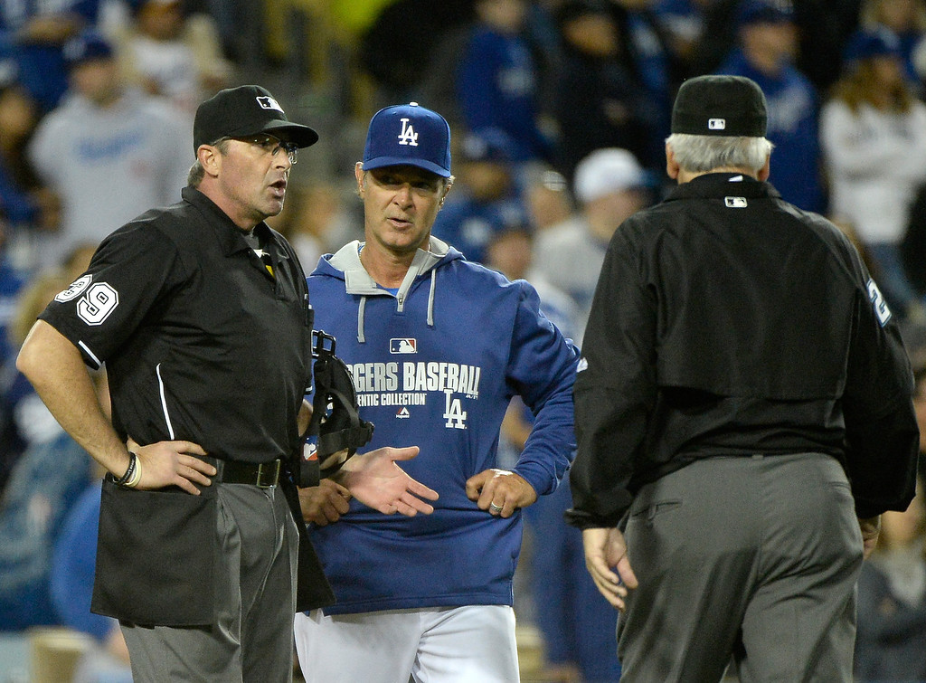 . LOS ANGELES, CA - APRIL 26:  Don Mattingly #8 of the Los Angeles Dodgers speaks to home plate umpire Paul Nauert and second base umpire Larry Vanover about the Dodger sixth run against the Colorado Rockies during the eighth inning at Dodger Stadium on April 26, 2014 in Los Angeles, California.  (Photo by Harry How/Getty Images)
