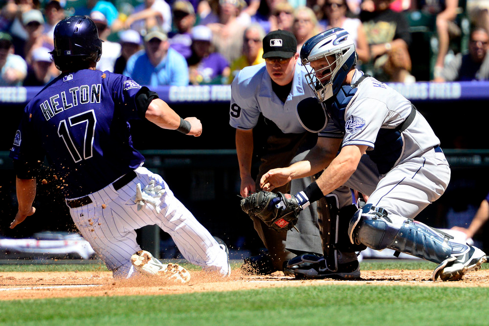 . San Diego Padres catcher Nick Hundley (4) applies a tag on Colorado Rockies first baseman Todd Helton (17) after he tried to tag and score on a sacrifice fly during the second inning in Denver. The Colorado Rockies hosted the San Diego Padres at Coors Field on Sunday, June 9, 2013. (Photo by AAron Ontiveroz/The Denver Post)