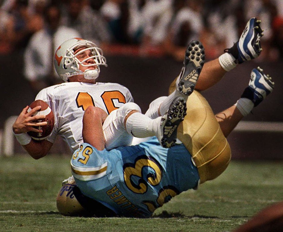 . UCLA linebacker Brian Willmer, #33,  blitzes Tennessee quarterback Peyton Manning, #16, for a sack during first quarter of Saturday\'s game. Manning went on to pass for 341 yards and two touchdowns in Tennessee\'s 30-24 victory over UCLA.  AP