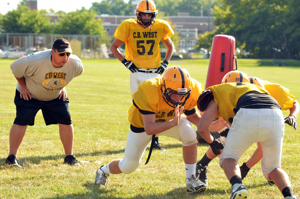. Central Bucks West football players at a morning practice.   At left is coach Brian Hensel.   Tuesday,  August 19, 2014.   Photo by Geoff Patton