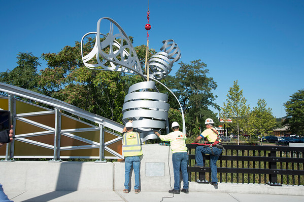 09/03/19 Wesley Bunnell | Staff The final bee statue was hoisted into place onto the Bee Hive Bridge by Sign Pro on Tuesday September 3, 2019. Install Manager Rob Mulcunry, L and Sign Pro President Peter Rappoccio help hold the bee steady as Spencer Brown climbs over the fence to bolt it into place.