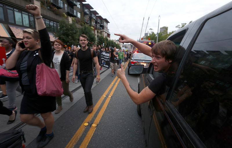 A driver yells his support of the Black Lives Matter march in recognition of the two year anniversary of the death of Michael Brown in Seattle, WA on August 9, 2016. Brown was an unarmed 18-year-old black teenager shot and killed by a white police officer in Ferguson, Missouri on Aug. 9, 2014.