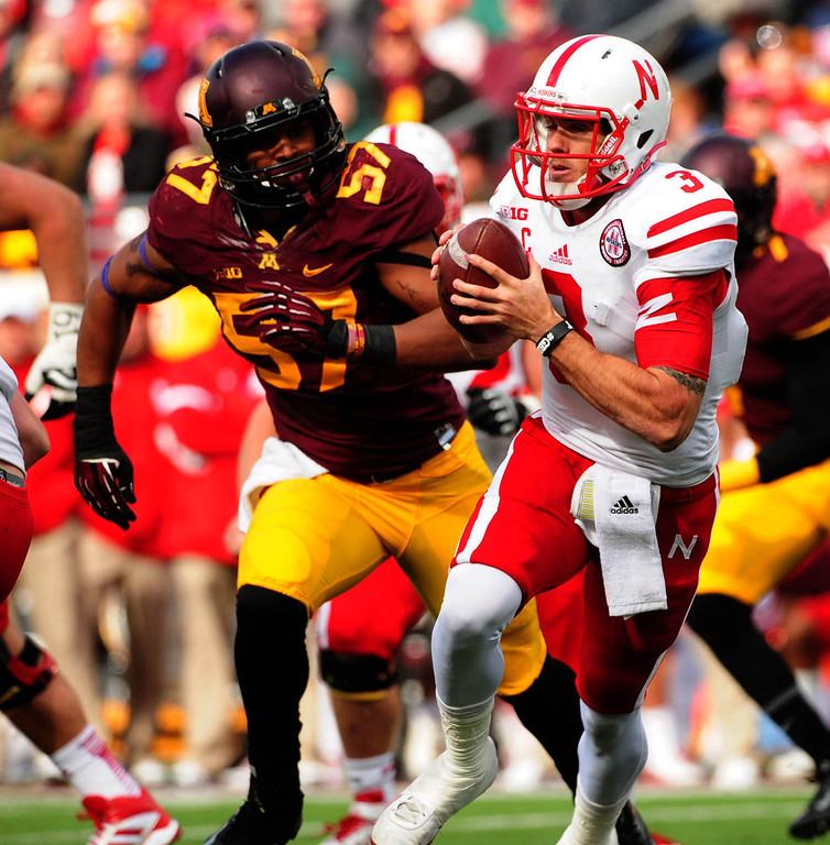 . Nebraska quarterback Taylor Martinez is chased by Minnesota\'s linebacker Aaron Hill in the third quarter. (Pioneer Press: Scott Takushi)