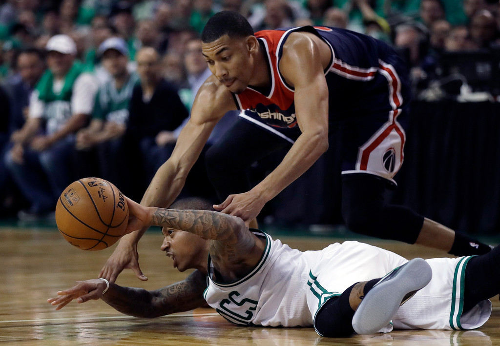 . Boston Celtics guard Isaiah Thomas makes a pass while sprawled on the floor as Washington Wizards forward Otto Porter Jr., top, defends during the second quarter of Game 7 of a second-round NBA basketball playoff series, Monday, May 15, 2017, in Boston. (AP Photo/Charles Krupa)