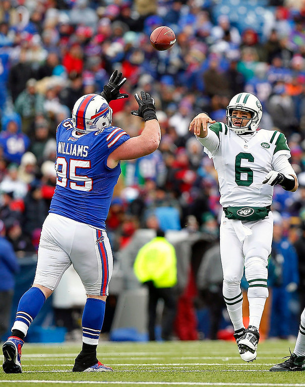 . New York Jets quarterback Mark Sanchez (6) passes under pressure from Buffalo Bills defensive tackle Kyle Williams (95) during the first half of an NFL football game on Sunday, Dec. 30, 2012, in Orchard Park, N.Y. (AP Photo/Bill Wippert)