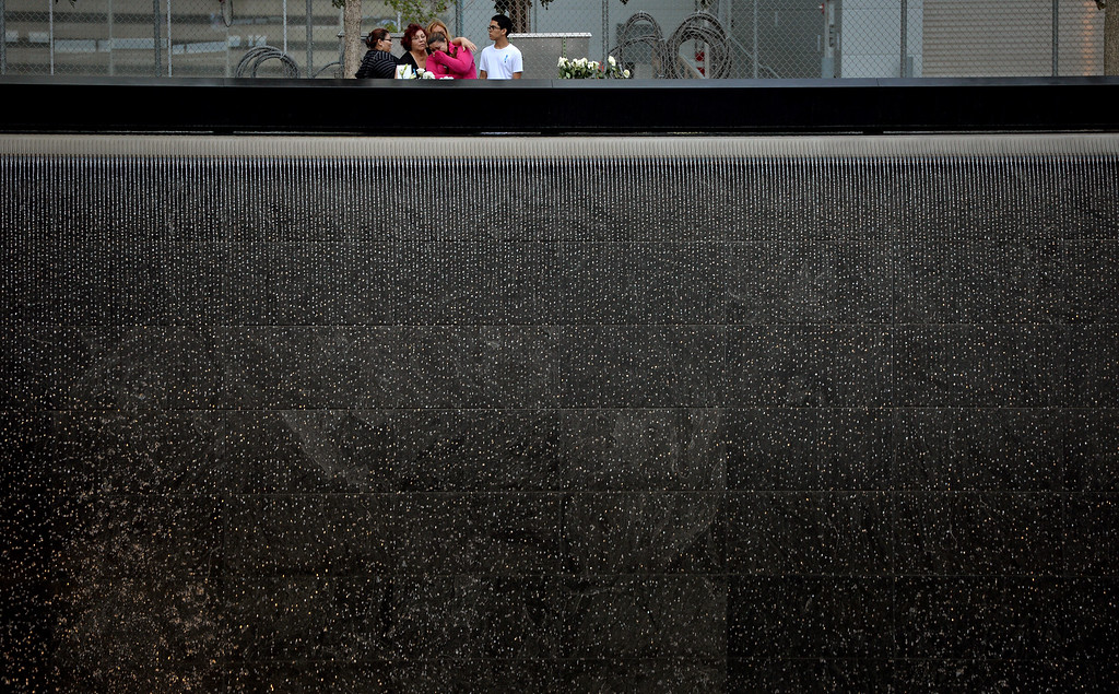 . A family stands at the edge of the North Pool during memorial observances on the 13th anniversary of the Sept. 11 terror attacks on the World Trade Center in New York, Thursday, Sept. 11, 2014.   In New York, family members of those killed at the World Trade Center will read the names of the victims at a ceremony at ground zero.  (AP Photo/Justin Lane, Pool)