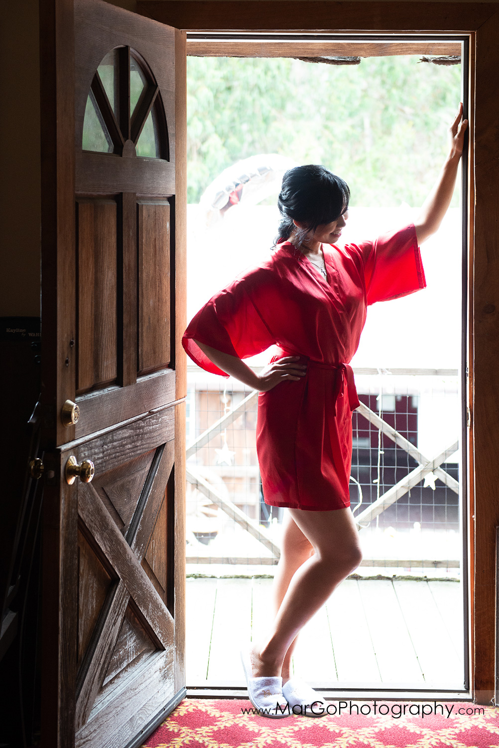 bride in red robe standing in doorway at Long Branch Saloon & Farms in Half Moon Bay