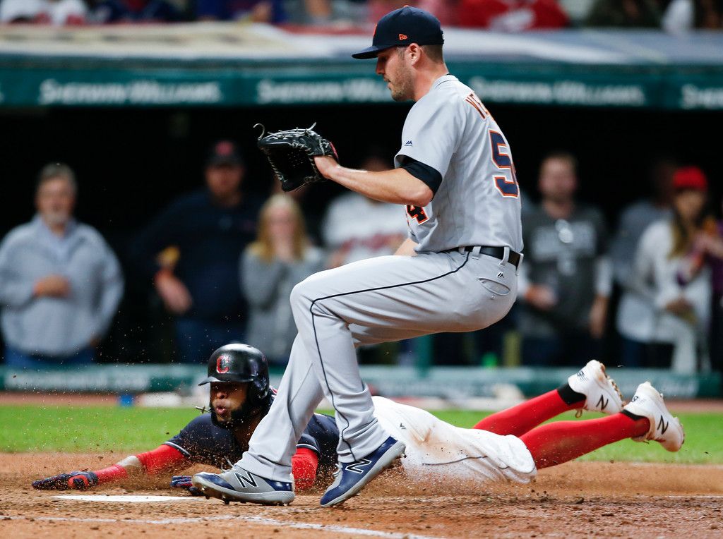 . Cleveland Indians\' Carlos Santana scores on a wild pitch by Detroit Tigers relief pitcher Drew VerHagen during the sixth inning in a baseball game, Tuesday, Sept. 12, 2017, in Cleveland. (AP Photo/Ron Schwane)