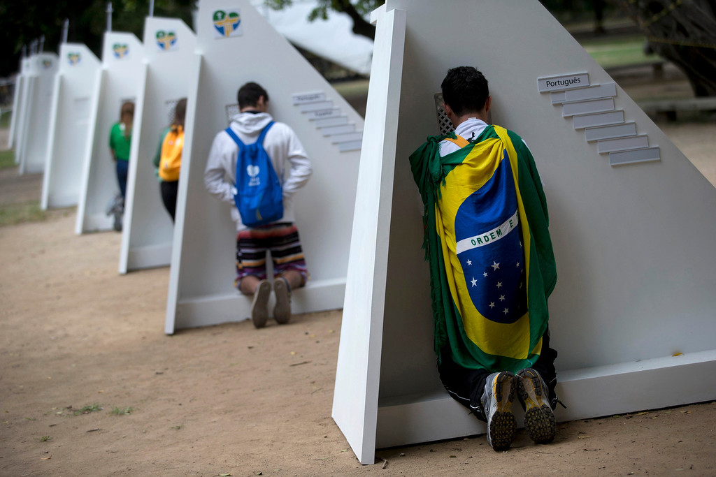 . Catholics kneel at portable confessionals set up in Quinta da Boa Vista park during World Youth Day events in Rio de Janeiro, Brazil, Tuesday, July 23, 2013. As many as 1 million young people from around the world are expected in Rio for the Catholic youth event.  (AP Photo/Silvia Izquierdo)
