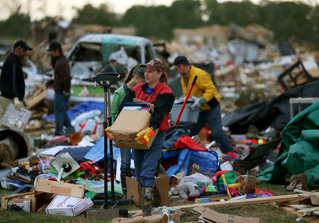 . Volunteer Gina Lowe (C) helps a family move belongings from a home that was destroyed by a tornado on Sunday, April 29, 2014 in Vilonia, Arkansas.  (Photo by Mark Wilson/Getty Images)