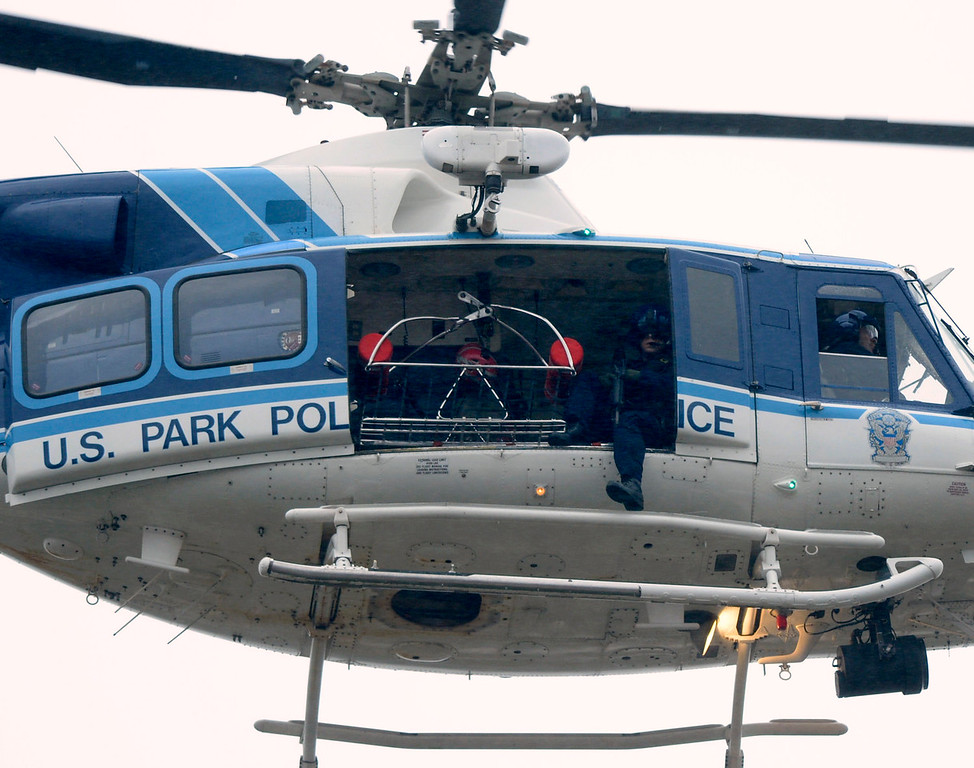 """. A U.S. Park Police helicopter flies over a building at the Washington Navy Yard in Washington, Monday, Sept. 16, 2013. President Barack Obama is mourning what he called \""""yet another mass shooting\"""" in the United States that he says took the life of American patriots. (AP Photo/Susan Walsh)"""