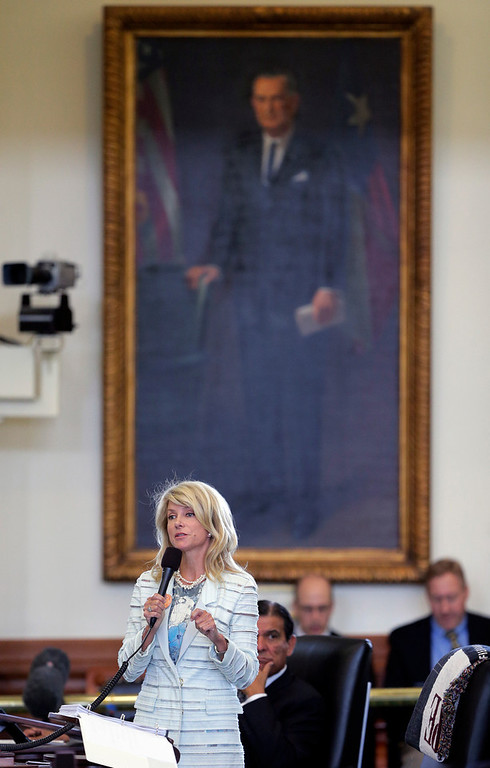 . Standing in front of a portrait of President Lyndon B. Johnson, Sen. Wendy Davis, D-Fort Worth, begins a filibuster in an effort to kill an abortion bill, Tuesday, June 25, 2013, in Austin, Texas. The bill would ban abortion after 20 weeks of pregnancy and force many clinics that perform the procedure to upgrade their facilities and be classified as ambulatory surgical centers.  (AP Photo/Eric Gay)