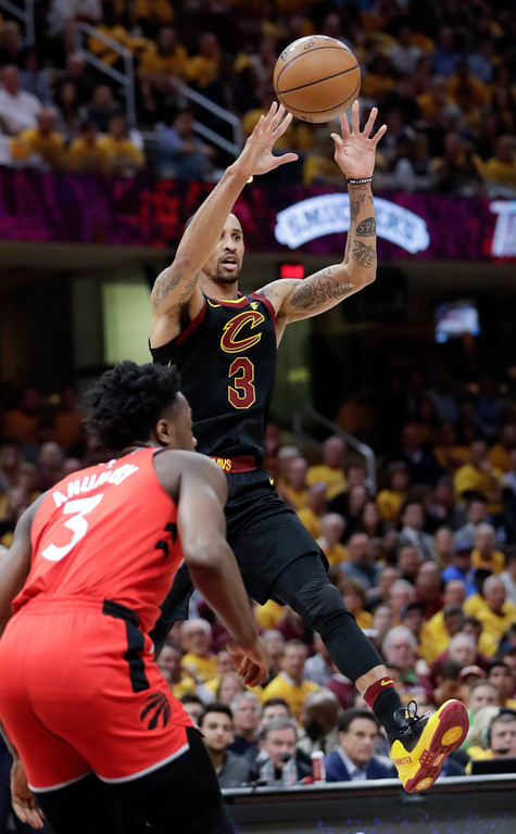 . Cleveland Cavaliers\' George Hill passes over Toronto Raptors\' OG Anunoby in the first half of Game 4 of an NBA basketball second-round playoff series, Monday, May 7, 2018, in Cleveland. (AP Photo/Tony Dejak)